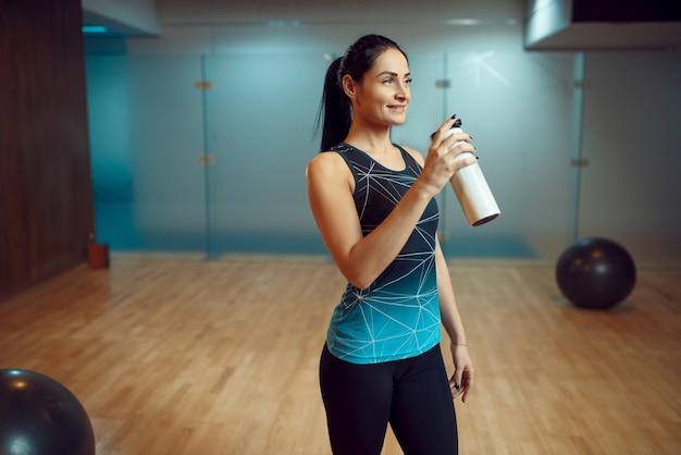 Femme souriante boit de l'eau après une formation de pilates dans une salle de sport, mode de vie sain. workuot de remise en forme dans un club de sport.