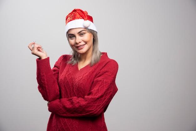 Femme souriante en bonnet de noel posant sur fond gris.