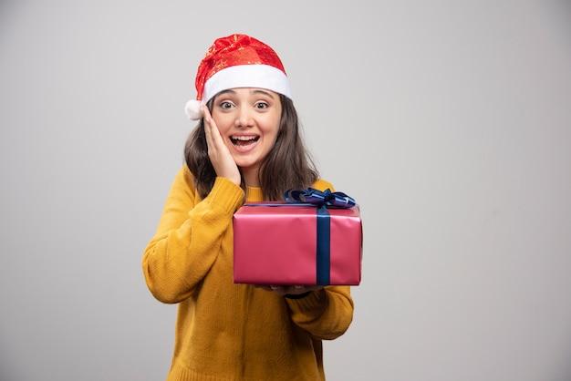 Femme souriante en bonnet de noel tenant une boîte-cadeau.