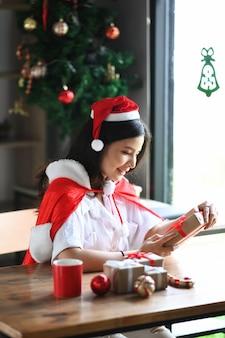 Femme souriante en bonnet de noel tenant un cadeau de noël.