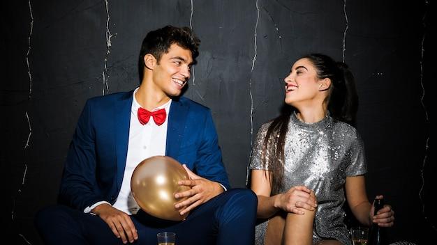 Femme souriante avec une bouteille près d'un homme heureux avec ballon