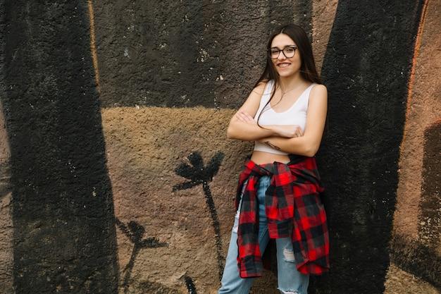 Femme souriante avec les bras croisés debout devant le mur