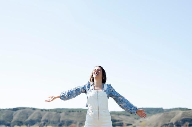 Femme souriante à bras ouverts et ciel bleu en arrière-plan