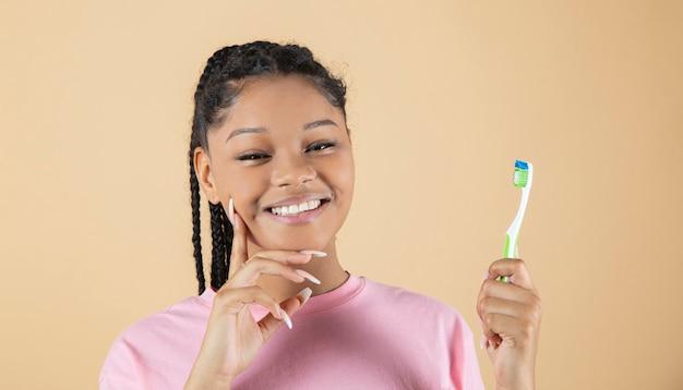 Femme souriante avec brosse à dents à la main sur fond jaune