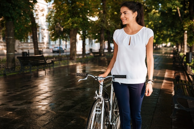Femme souriante brune décontractée marchant dans le parc de la ville à vélo