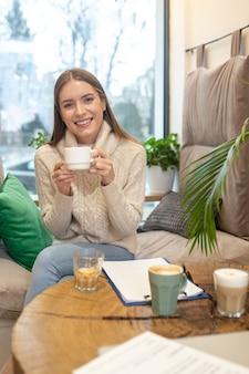 Une femme souriante buvant beaucoup de café tout en travaillant