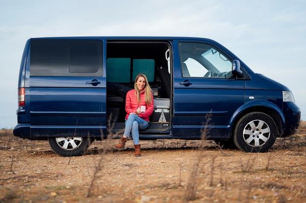 Femme souriante buvant du café dans la camionnette