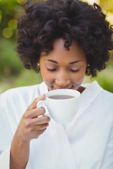Femme souriante, buvant du café dans le jardin