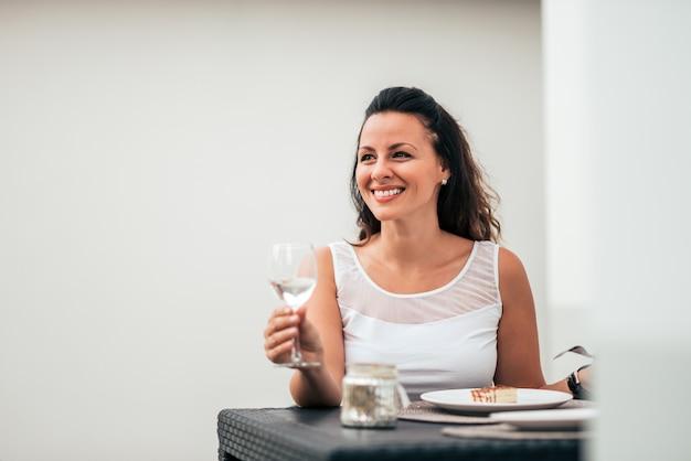 Femme souriante, buvant un verre de vin et mangeant un gâteau. fermer.