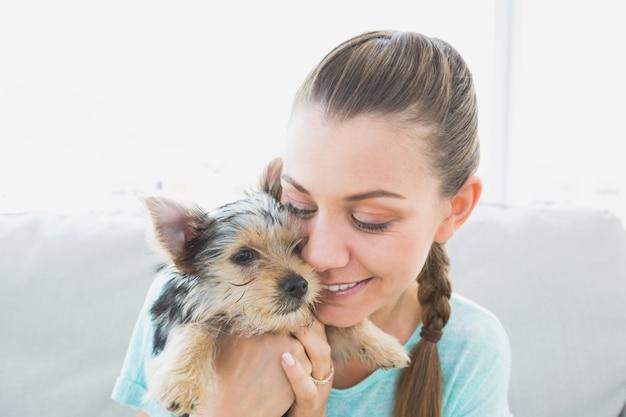 Femme souriante câlins son chiot yorkshire terrier