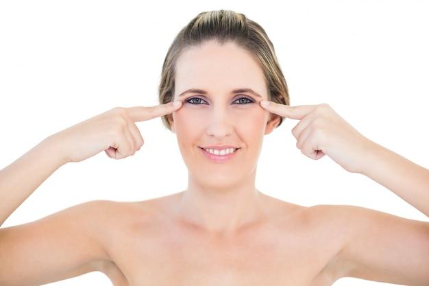 Femme souriante à la caméra montrant des rides sur ses yeux