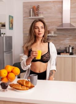 Femme souriante à la caméra pendant le petit déjeuner portant une lingerie noire séduisante. jeune femme blonde séduisante sexy avec des tatouages buvant du jus d'orange fait maison sain et naturel, rafraîchissant dimanche matin