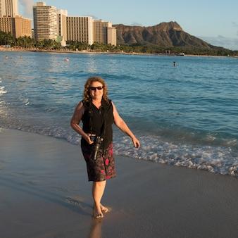 Femme souriante avec une caméra sur la plage, waikiki, honolulu, oahu, hawaii, états-unis