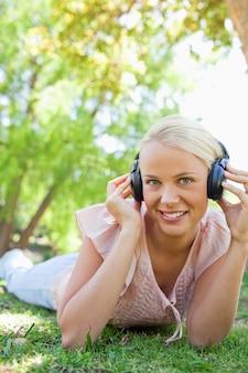 Femme souriante avec un casque en appréciant la musique sur l'herbe