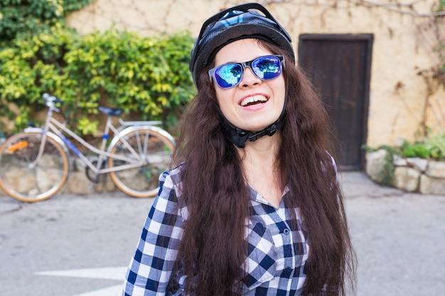 Femme souriante avec casque et lunettes de soleil position sur vélo mural et ruelle.
