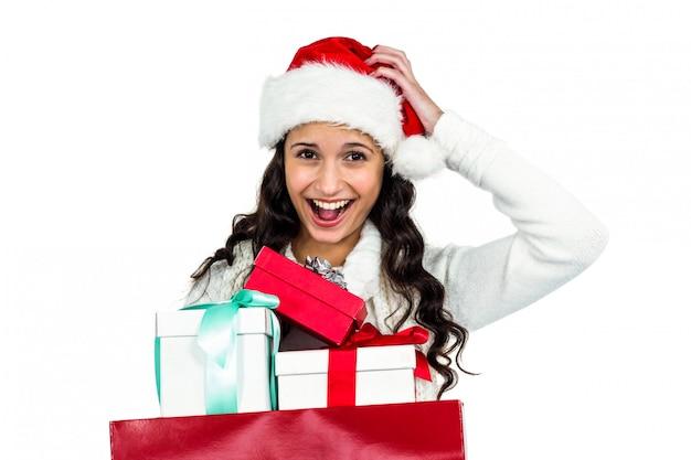 Femme souriante avec un chapeau de noël tenant des cadeaux