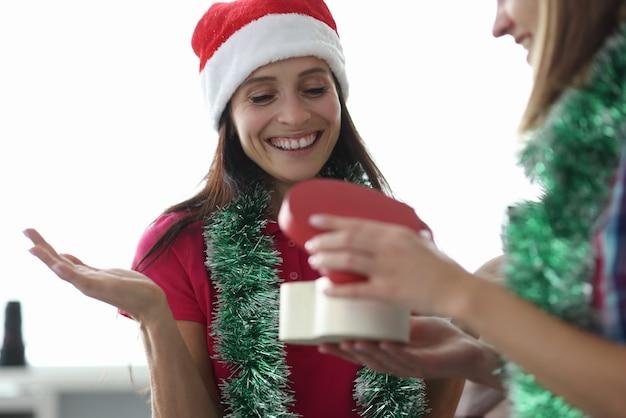 Femme souriante en chapeau de père noël regarde la boîte-cadeau
