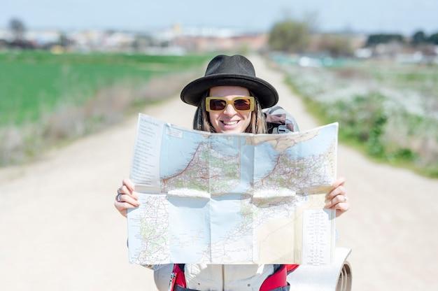 Femme souriante avec chapeau tenant une carte sur une route