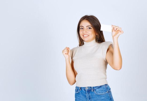 Femme souriante en chemise beige montrant sa carte sur fond blanc.