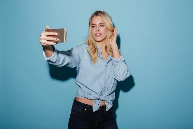 Femme souriante en chemise posant et faisant selfie sur smartphone