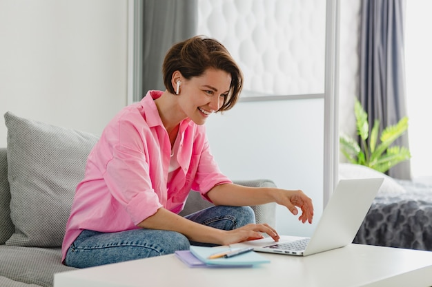 Femme souriante en chemise rose assis détendu sur un canapé à la maison à table travaillant en ligne sur un ordinateur portable à la maison