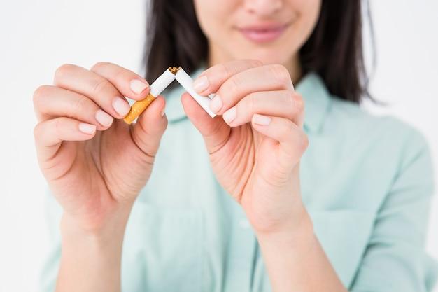 Femme souriante claquant une cigarette en deux