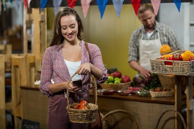 Femme souriante en cliquant sur l'image de tomates dans le panier