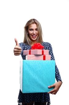 Femme souriante avec des coffrets cadeaux et montrant le pouce vers le haut