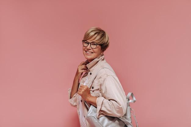 Femme souriante avec une coiffure blonde élégante, des lunettes et un sac gris en veste moderne beige regardant dans la caméra sur fond rose.