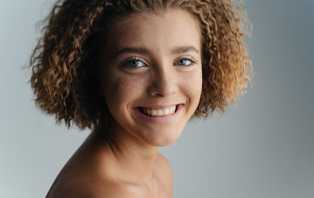Femme Souriante Coiffure Bouclée Nue épaules Gros Plan. Photo De Haute Qualité Photo Premium