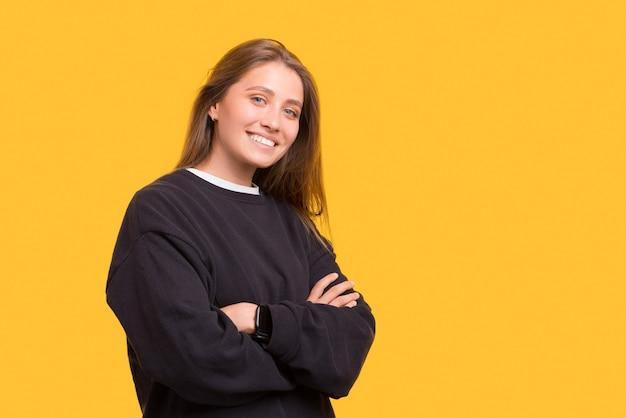 Une femme souriante et confiante regarde la caméra avec les bras croisés.