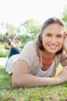 Femme souriante, couché sur l'herbe