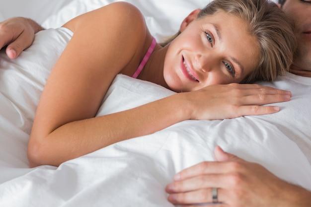 Femme souriante couchée sur la poitrine des maris au lit