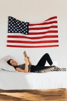 Femme souriante, coucher lit, et, utilisation tablette