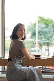 Femme souriante de coup moyen assise avec du café