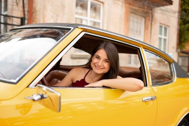 Femme souriante de coup moyen au volant d'une voiture