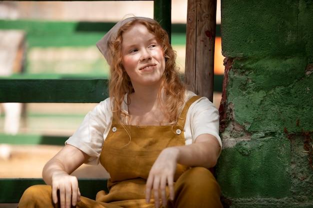 Femme souriante de coup moyen à la ferme