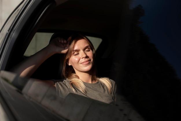 Femme souriante de coup moyen à l'intérieur de la voiture