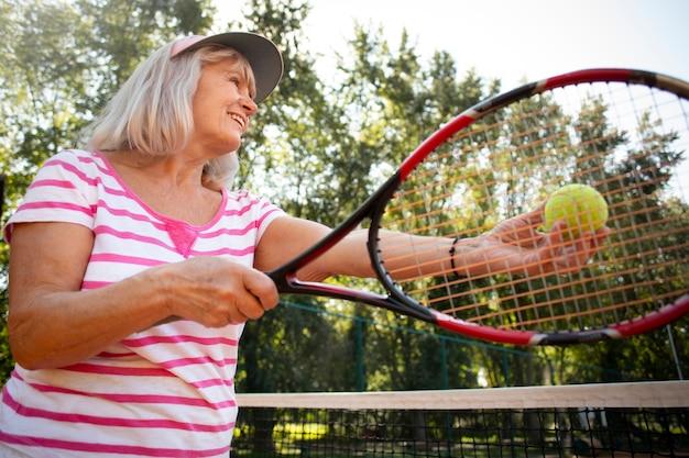 Femme souriante de coup moyen jouant au tennis