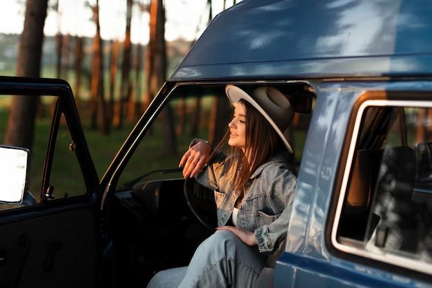 Femme souriante de coup moyen posant dans une camionnette