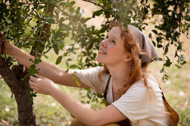 Femme souriante de coup moyen près de l'arbre