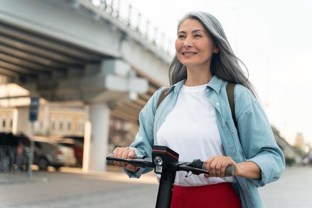 Femme souriante de coup moyen avec scooter
