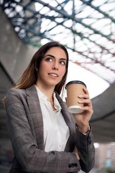 Femme souriante de coup moyen avec une tasse de café