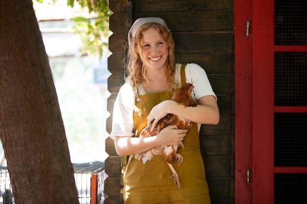 Femme souriante de coup moyen tenant une poule