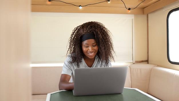 Femme souriante de coup moyen travaillant sur un ordinateur portable