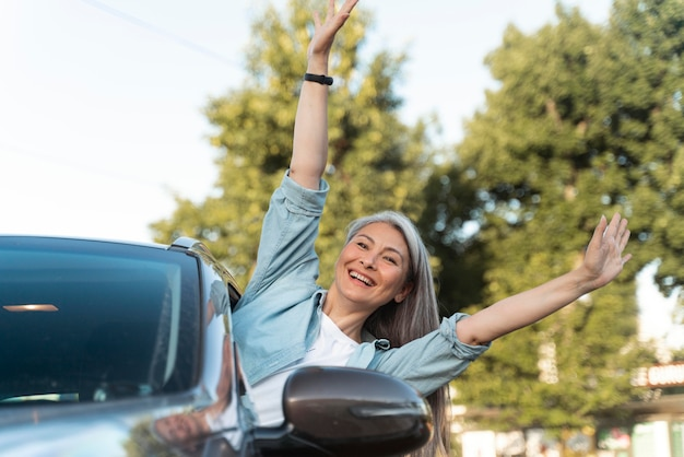 Femme souriante de coup moyen en voiture