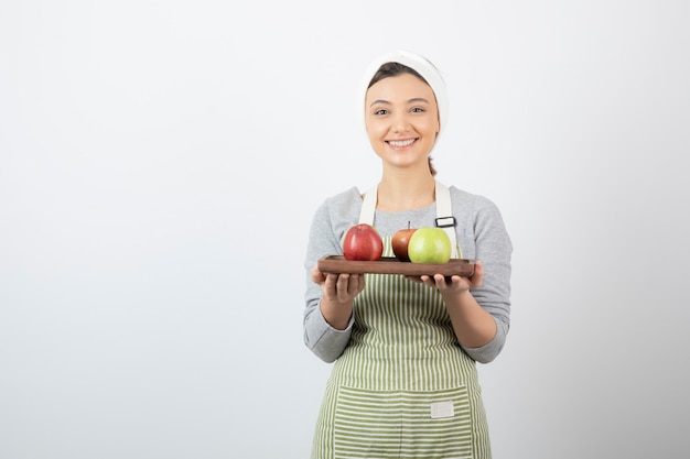 Femme souriante cuisinier tenant une assiette de pommes sur blanc.