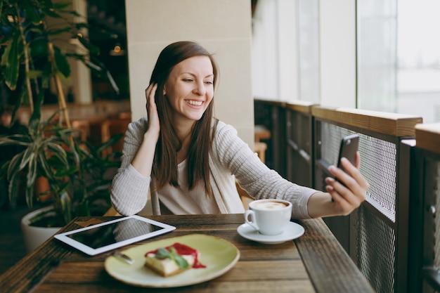 Femme souriante dans un café avec une tasse de cappuccino, gâteau, faisant du selfie sur téléphone portable, se relaxant au restaurant pendant le temps libre. femme assise avec ordinateur tablette pc reste au café. concept de mode de vie