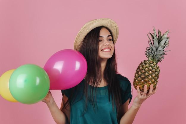 Femme souriante dans un chapeau pose avec des ballons colorés et un ananas