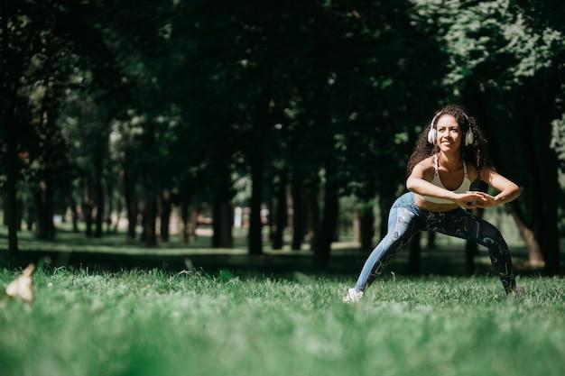 Femme souriante dans les écouteurs faisant des étirements avant de faire du jogging outd